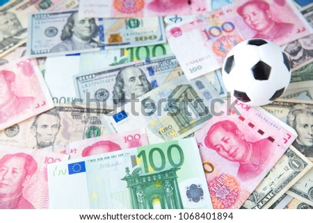 soccer ball over a lot of money. corruption football game. Betting and gambling concept. wold cup 2018. European cup . UEFA Champions League. premier league. bundesliga. la liga. calcio serie a. #1068401894