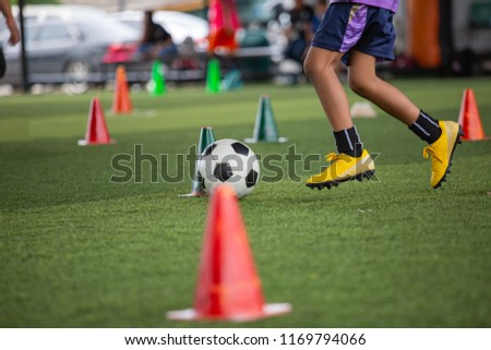 Soccer ball tactics a boy on grass field with cone ball control skill for training children in Soccer academy