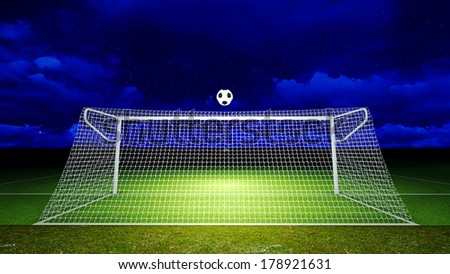 Soccer ball was floated into the goal on the football field at night.