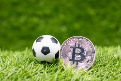 Soccer ball with bitcoin are on green grass for sport betting concept