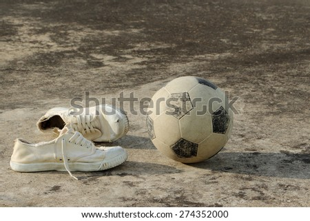 soccer ball with canvas shoes on concrete floor (street soccer background)