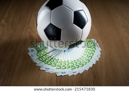 Soccer ball with fan of euro banknotes on hardwood floor.