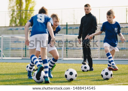 Soccer camp for kids. Boys practice football dribbling in a field. Players develop soccer dribbling skills. Children training with balls. Soccer slalom drills to improve football dribbling pace #1488414545