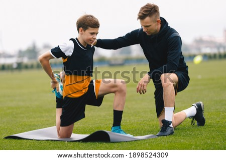 Soccer Coach With Young Player. Boy on Football Field Stretching on Exercise Mat. Male Coach and Personal Trainer Giving Advices to Young Athlete Foto stock ©