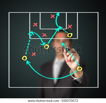 soccer coach writing strategy of attacking game