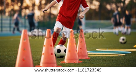 Soccer Drills: The Slalom Drill. Youth soccer practice drills. Young football player training on pitch. Soccer slalom cone drill. Boy in red soccer jersey shirt running with ball between cones