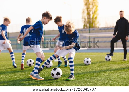 Soccer Education for Young Boys. Physical Education Class for School Children. Young Coach With Kids in Team on Training Unit. Youth Team Coach Training School Boys in Football Soccer