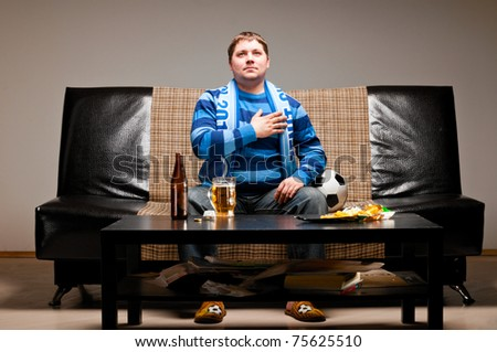 soccer fan is sitting on sofa and listening for a hymn with beer at home