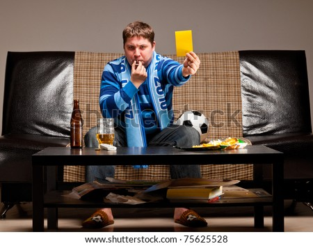 soccer fan is sitting on sofa with beer and showing yellow card at home
