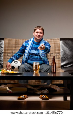 soccer fan is sitting on sofa with beer at home