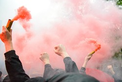 Soccer fans holding up fireworks with thick red smoke of bengal fire