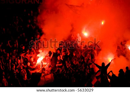 Soccer fans with alight the torches at the stadium