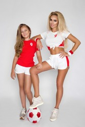 Soccer fans. Young girls football player. Beautiful body of fitness models with soccer ball isolated on white background. Pretty football girls, mother and daughter.  Family cheering, football.