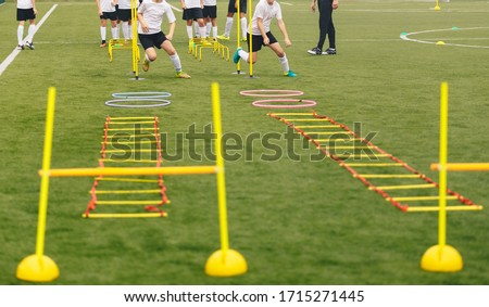 Soccer field with training equipment and players with coach in background. Junior football team training and coach. Sport team on training. Football training equipment: ladder, hula hoop, hurdle, cone