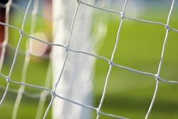 Soccer football equipment. White soccer net on a goal. Soccer net nodes. Blurred goal post in the background