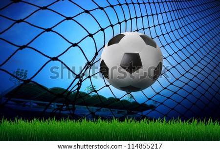 soccer football in goal net and stadium blue sky background