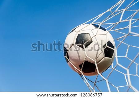 Soccer football in Goal net with Blue sky field.