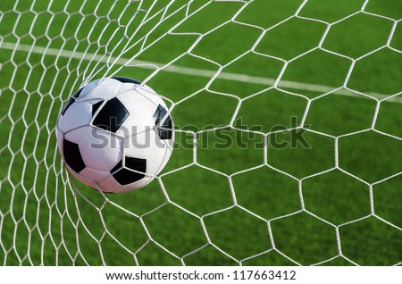 Soccer football in Goal net with green grass field.