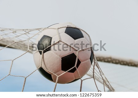Soccer football in Goal net with sky field.