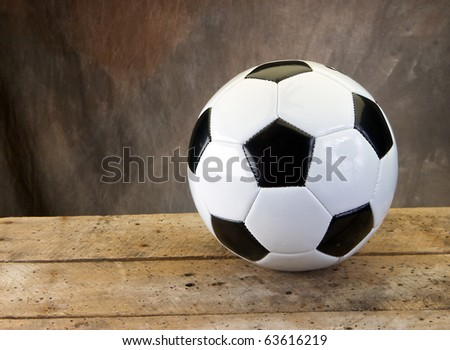 Soccer football on old vintage wood table with tan background and copy space