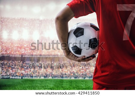 soccer football player in red team concept holding soccer ball in the stadium #429411850