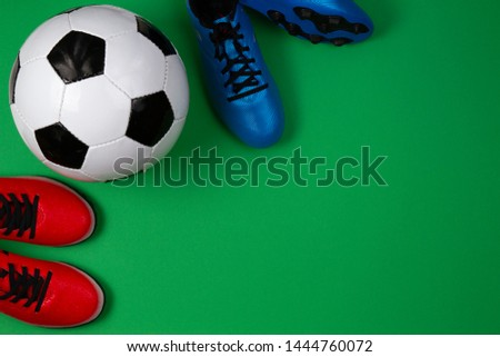 Soccer football sport background. Top view to soccer ball and boots on green background #1444760072