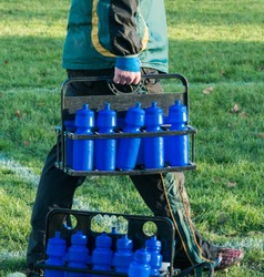 Soccer football team's water in reusable blue bottles; carried onto the pitch by a coach wearing a green and yellow jacket.