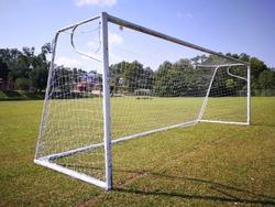 Soccer goal on the football field with blue sky.