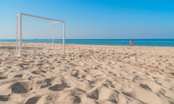 Soccer goal post on the beach with sand and blue sky