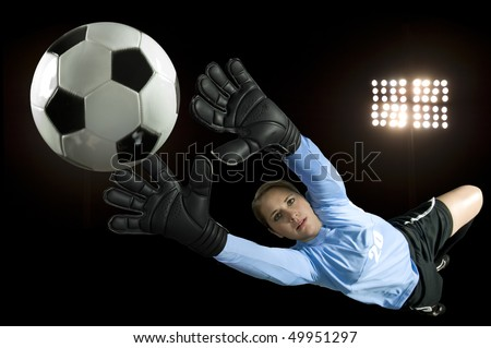 soccer goalie blocks ball in stadium