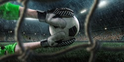 Soccer goalkeeper catches a ball. View through the football goal. Behind him a big rainy professional arena. Goalkeeper wears unbranded clothes.