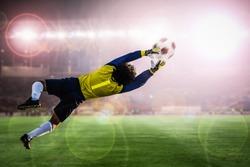 soccer goalkeeper catches the ball on stadium light background