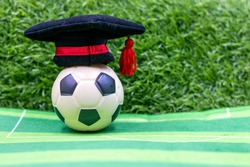 Soccer graduation with hobo hat on green grass background