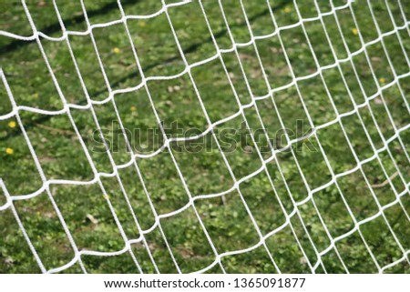 Soccer net against green field background #1365091877