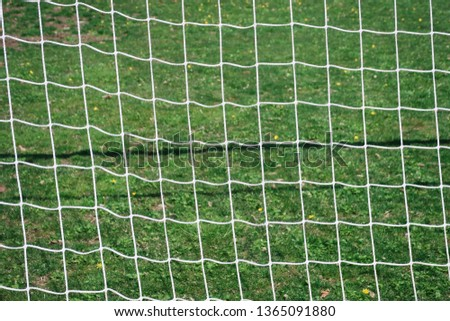 Soccer net against green field background #1365091880