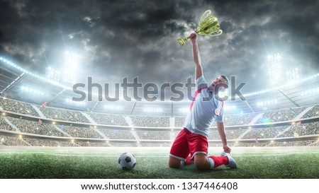 Soccer player celebrates winning the open stadium. Soccer player holds a trophy one hand . Medal on the neck. The winner of the soccer cup. Strong soccer joy