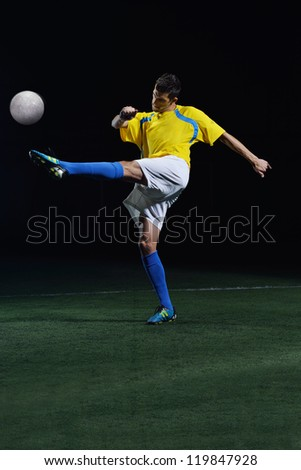soccer player doing kick with ball on football stadium  field  isolated on black background