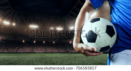 Soccer player holds a soccer ball on a professional stadium
