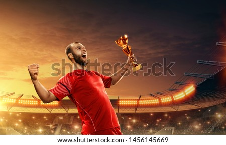 Soccer player holds champions cup and celebrates victory on a night floodlit soccer stadium. Emotional shot #1456145669