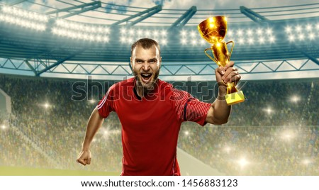 Soccer player holds champions cup and celebrates victory on a night floodlit soccer stadium. Emotional shot
