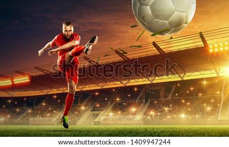 Soccer player in action. Kick off the ball. Running shot. Floodlit night stadium