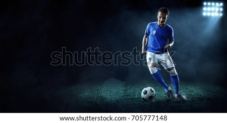 Soccer player in action on a dark background #705777148