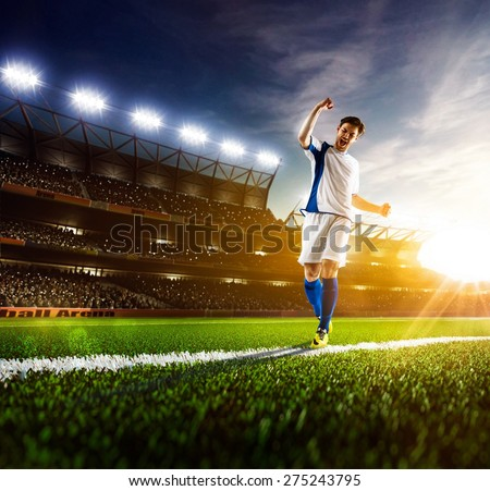Soccer player in action on night stadium panorama background
