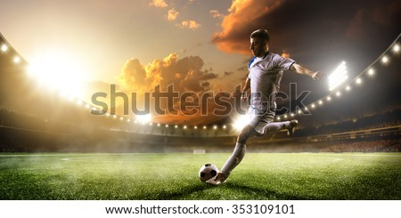 Soccer player in action on sunset stadium background #353109101