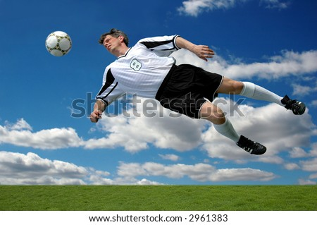 Soccer player in action shot heading the ball over a blue sky with clouds.