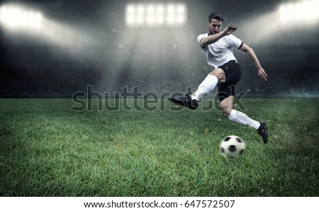 Soccer player is fighting for the ball in a stadium full with people #647572507