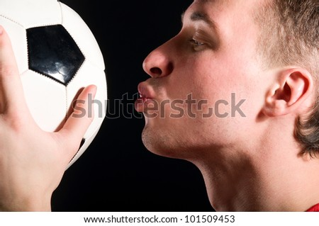 soccer player is kissing the ball in dark