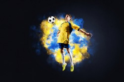 Soccer player jumping with ball in smoke. Sportsman in yellow and blue uniform in action. Soccer game championship concept with copy space. Young player on dark background. Movement at gameplay.