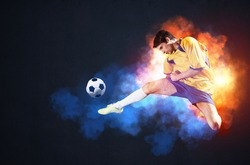 Soccer player kicking ball in colorful smoke. Sportsman in yellow and blue uniform in action. Soccer game championship concept with copy space. Young player on dark background. Movement at gameplay.