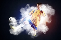 Soccer player kicking ball in white smoke. Sportsman in yellow and blue uniform in action. Soccer game championship concept with copy space. Young player on dark background. Movement at gameplay.